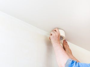melbourne paint renovation of apartment preparation of walls for painting Decorator fixes masking tape on wall before painting  Melbourne Paint