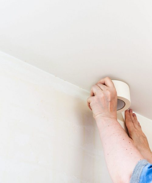 melbourne paint renovation of apartment - preparation of walls for painting. Decorator fixes masking tape on wall before painting